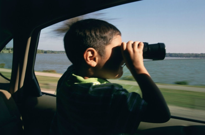 Kid looking through binoculars in motorhome